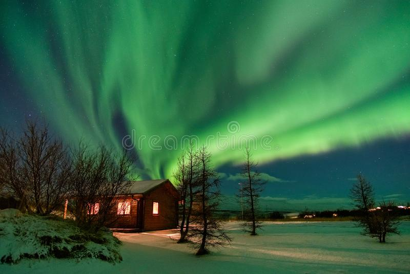 Aurora sobre la cabaña en Islandia foto de archivo