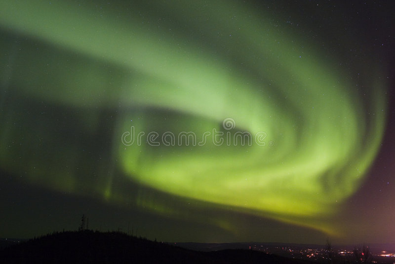 Aurora swirls over town royalty free stock image