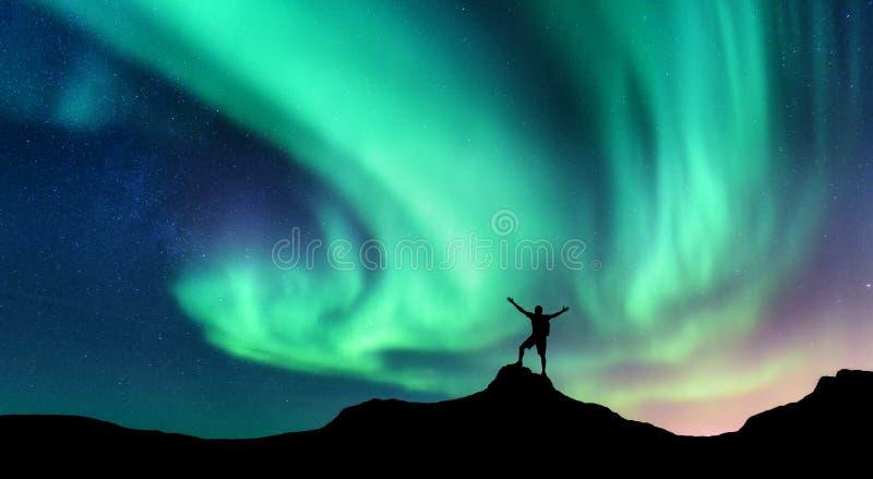 Aurora und Schattenbild des stehenden Mannes mit den angehobenen oben Armen auf dem Berg in Norwegen Aurora Borealis lizenzfreie stockfotos