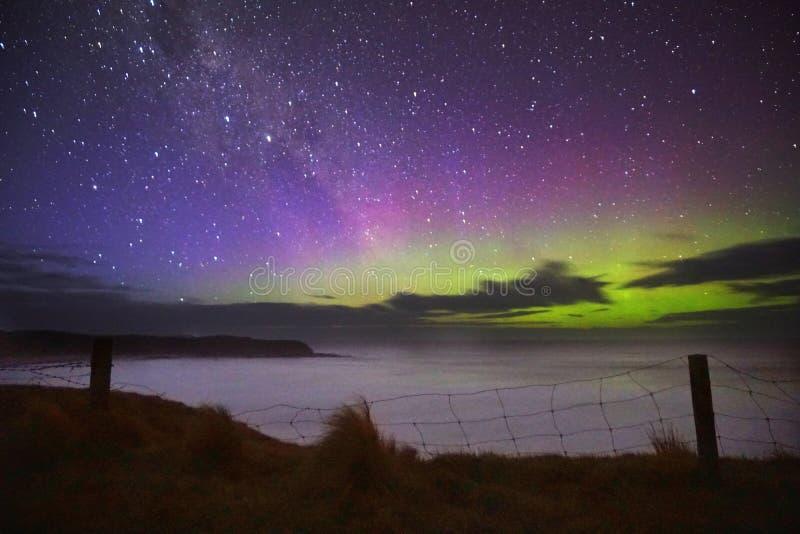 Aurora verde púrpura sobre la cerca del acantilado fotografía de archivo