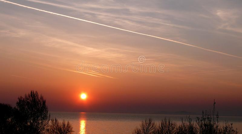 Auroral sky and chemtrail above Lake Balaton. Early morning just rises sun above Lake Balaton, lazy lights and airplane traces on stock photo