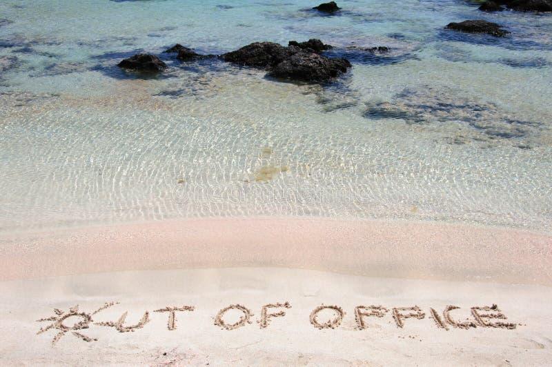 AUS DEM BÜRO heraus, das auf Sand auf einem schönen Strand geschrieben wird, bewegt Blau in Hintergrund wellenartig stockfotos