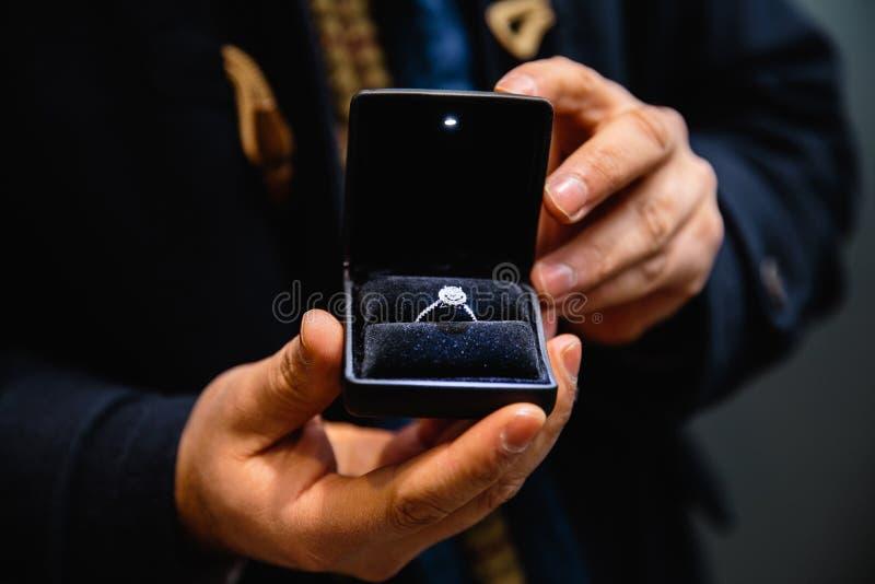Aus dem wirklichem Leben Antrag: Mann hält einen belichteten Verlobungsring - blauen Brautring mit einem großen Edelstein stockbild