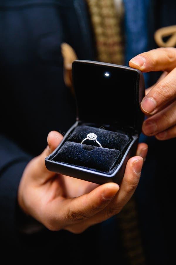 Aus dem wirklichem Leben Antrag: Mann hält einen belichteten Verlobungsring - blauen Brautring mit einem großen Edelstein stockfoto