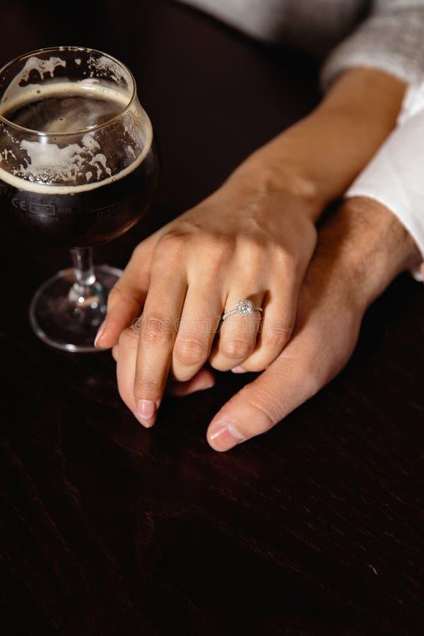 Aus dem wirklichem Leben Antrag: Verbinden Sie Händchenhalten in einer Kneipe mit einem Glas Bier zu ihrer Seite lizenzfreies stockbild