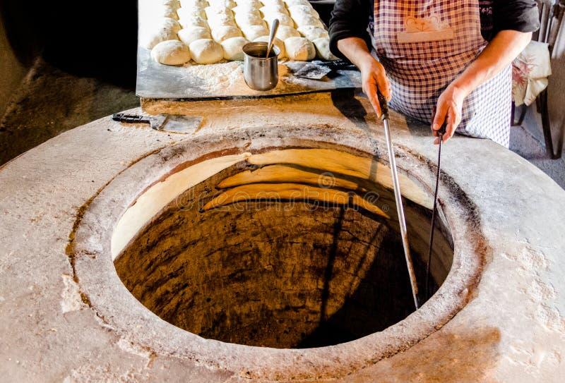 Aus einem traditionellen Ziegelsteinofen heraus Traditionelle georgische Brote C lizenzfreie stockfotografie