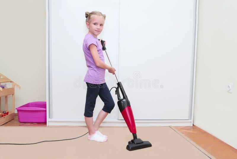 Ausbildung des Kinderkonzeptes, säubernd Reinigungsteppich des jungen blonden Mädchens in ihrem Raum mit Staubsauger lizenzfreies stockfoto