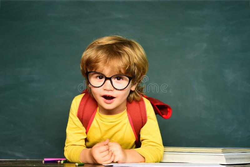 Ausbildung Kinder wird zur Schule fertig Lernen des Konzeptes Erster Schultag Gl?ckliche l?chelnde Sch?ler, die am Schreibtisch z stockfotos