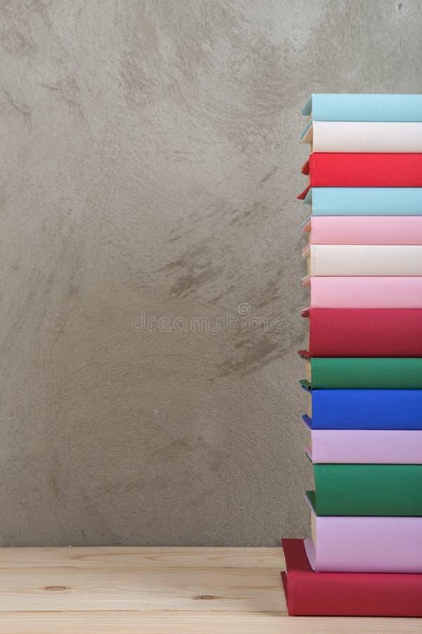 Ausbildung und Lesekonzept - Gruppe bunte Bücher auf dem Holztisch, Betonmauertafel stockfoto