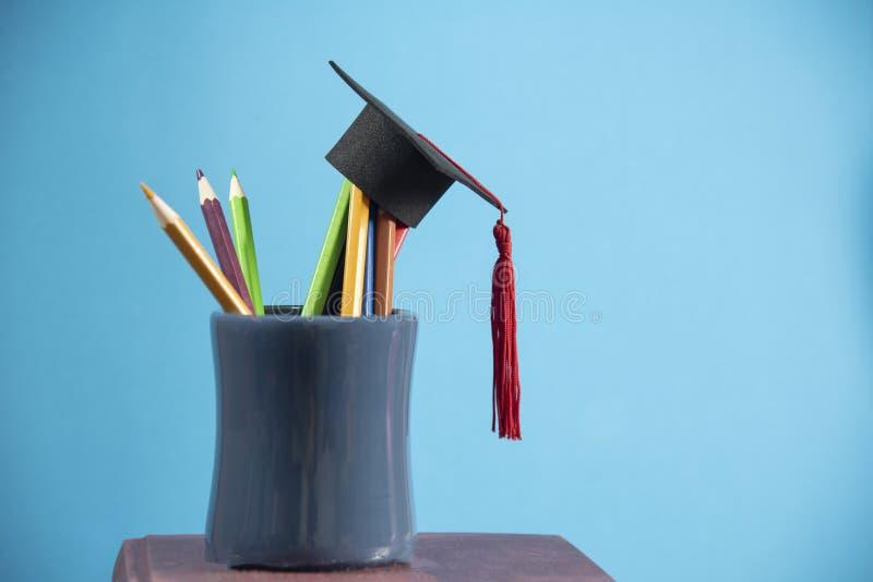 Ausbildung und zurück zu Schulkonzept mit Staffelungskappen-Bleistiftfarbe in einem Bleistiftkasten auf blauem Hintergrund lizenzfreie stockfotografie