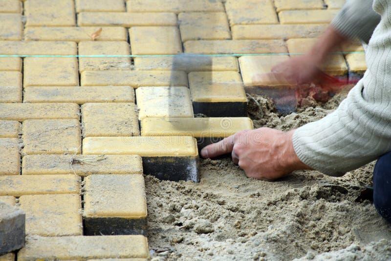 Ausbreitender Plattefußboden des Bauarbeiters lizenzfreie stockfotos