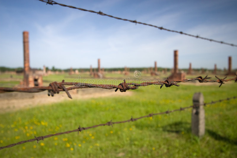 Auschwitz Birkenau. Barbed wire and chimney in background, Auschwitz Birkenau stock image