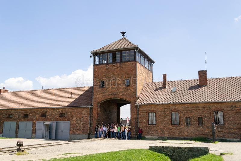Auschwitz-Birkenau, concentration camp, Poland. The security tower at the entrance to Auschwitz-Birkenau concentration camp, Poland with group of students making royalty free stock photography