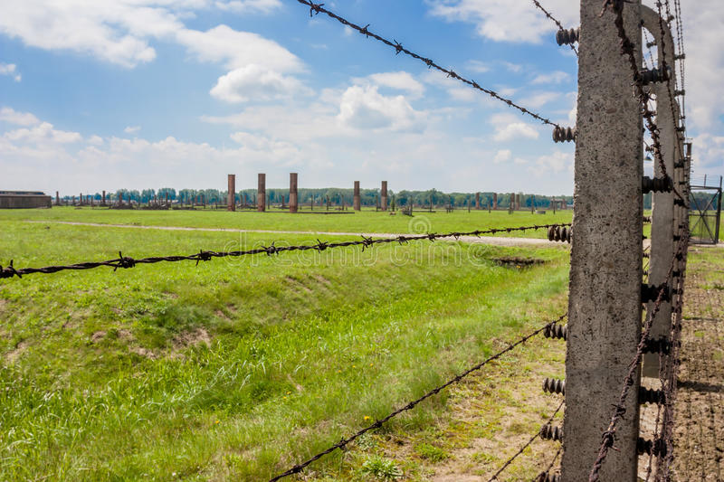Auschwitz concentration camp. AUSCHWITZ-BIRKENAU CONCENTRATION CAMP, KRAKOW, POLAND - CIRCA JUNE 2012: View of territory of with electric barbwire fence and royalty free stock images