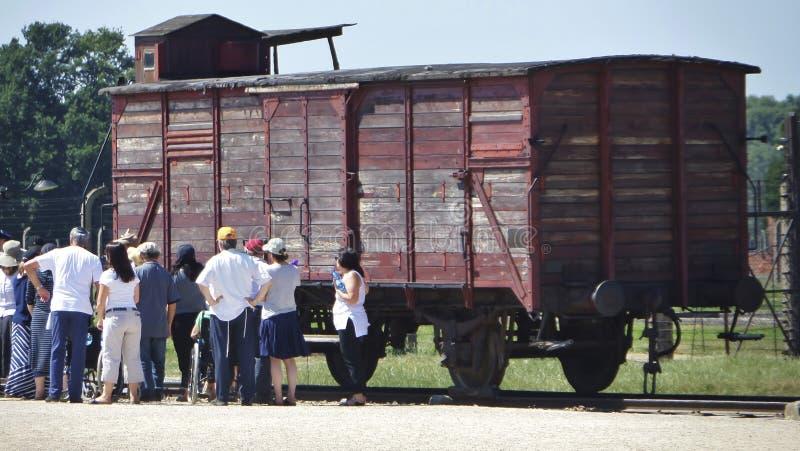 Auschwitz II - Birkenau, besökare som ser drevvagnen för fångetransport - Juli 6th, 2015 - Krakow, Polen arkivfoton
