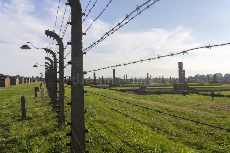Auschwitz II - Birkenau utrotningläger utomhus bak försedd med en hulling - trådstaket arkivfoton