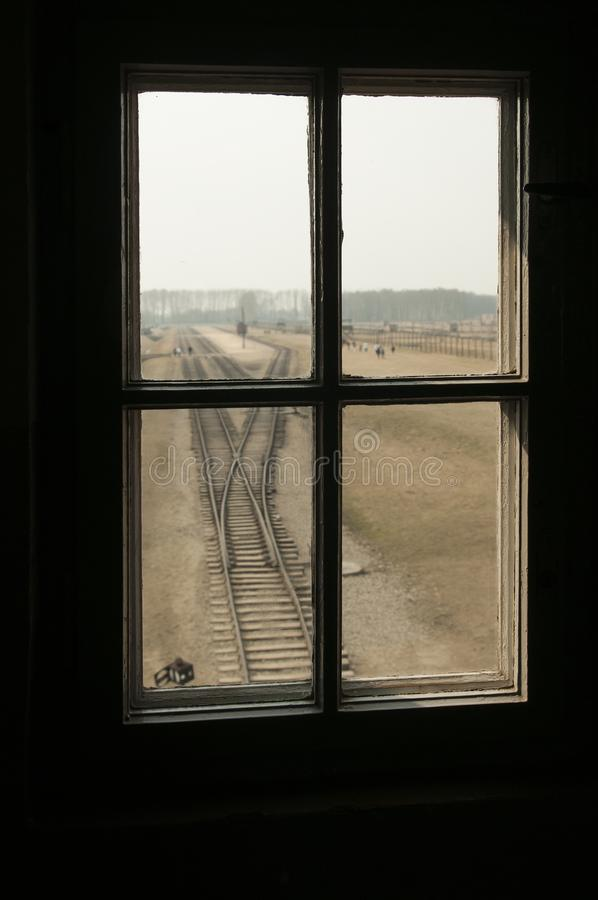 AUSCHWITZ, POLAND - March 30 2012 Melancholic view through a window of a concentration camp railway selection platform. And barracks stock image