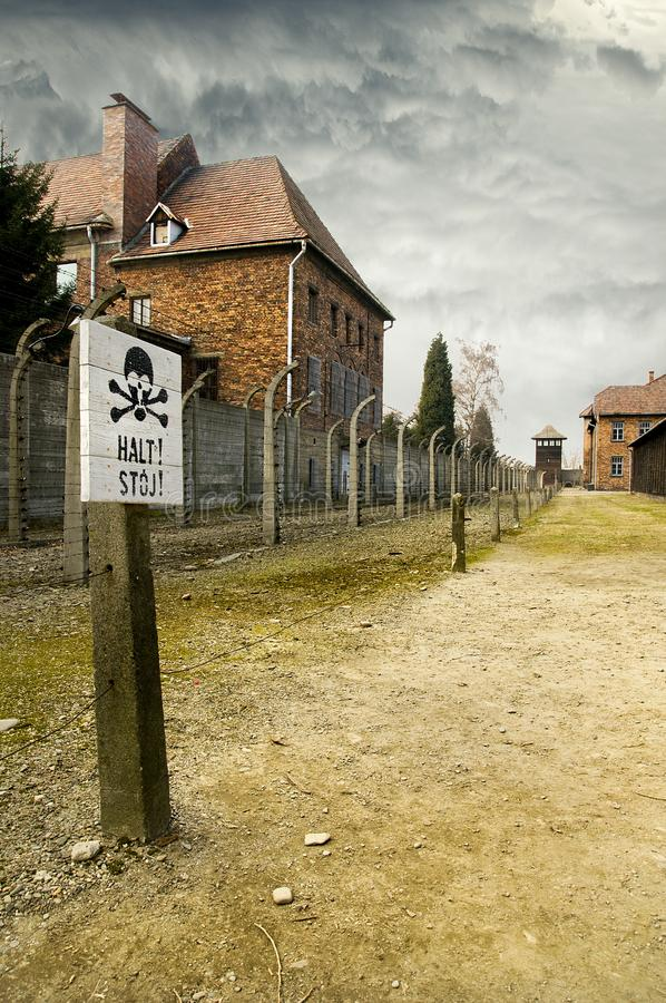 AUSCHWITZ, POLAND - March 30 2012: Sign with reading Stop in German and Polish in front of wired fence in Birkenau royalty free stock photo