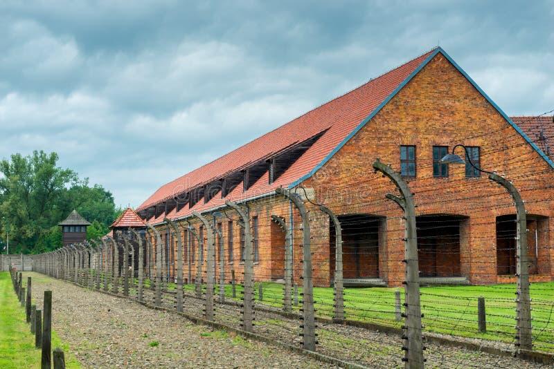 Auschwitz, Polen - Augustus 12, 2017: baksteenbarakken door prikkeldraad onder het concentratiekamp dat van spanningsauschwitz wo royalty-vrije stock foto