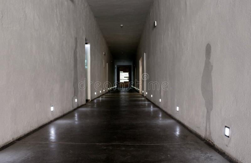 Auschwitz Polen - 06 15 2017: Långt perspektiv och skuggor på väggar i korridor av döduniversitetsområdet i den Auschwitz koncent arkivbild