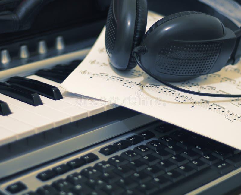 Auscultadores e folha de música no teclado fotos de stock royalty free