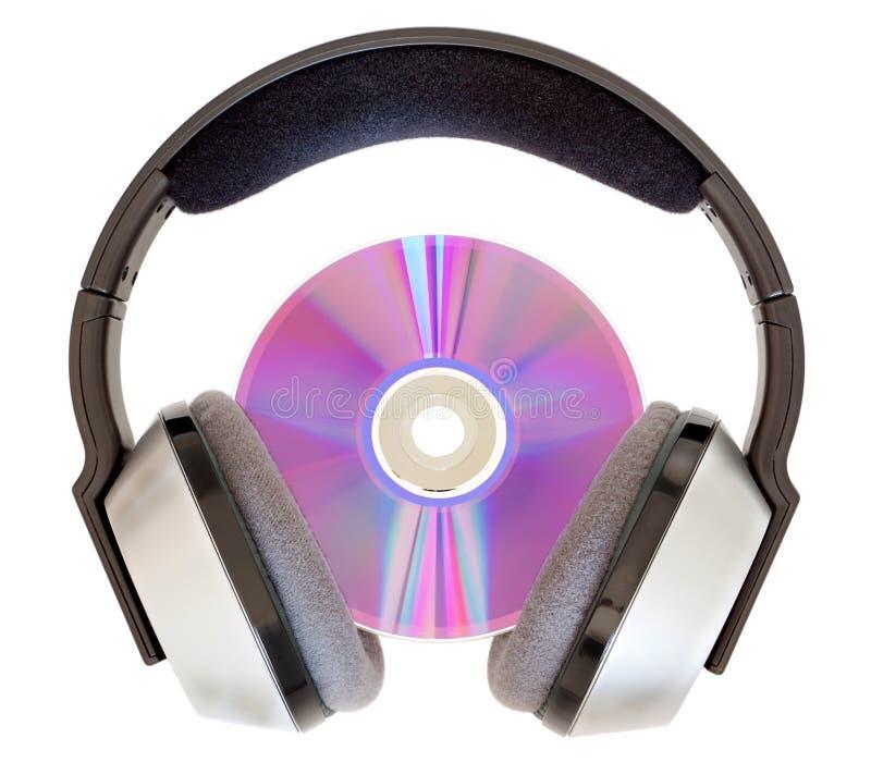 Auscultadores sem fio e um CD para escutar a música. fotografia de stock