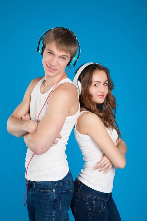 Auscultadores vestindo dos pares novos do amor, música de escuta foto de stock royalty free