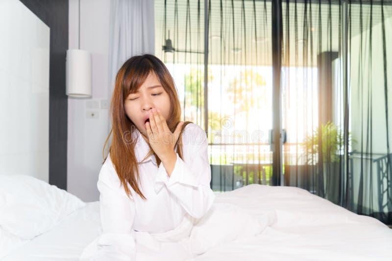 Ausdehnende und beim morgens aufwachen gähnende Frau stockfotos