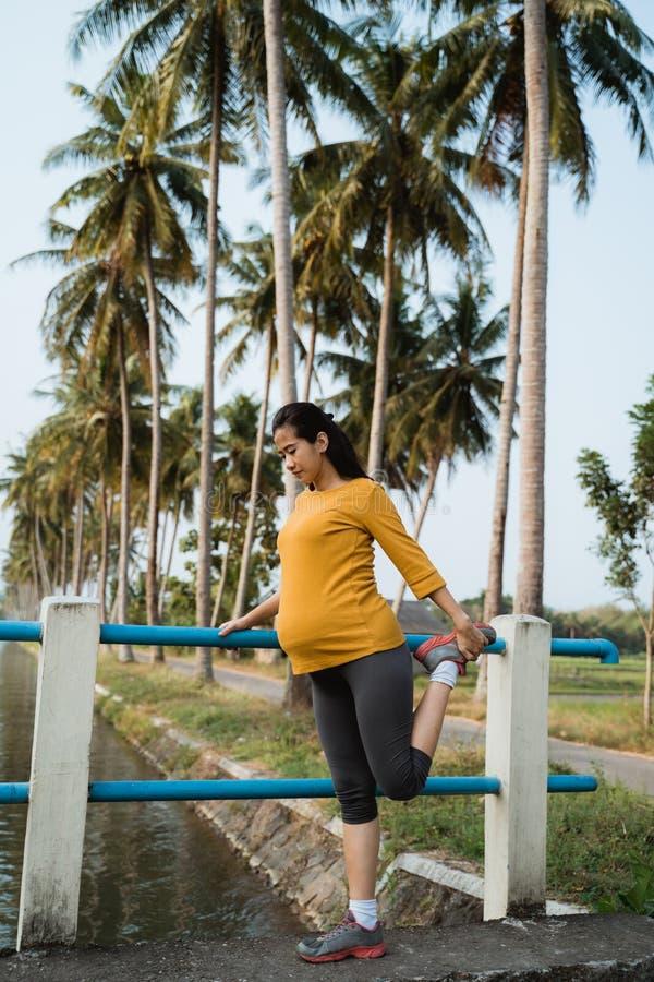 Ausdehnung der schwangeren Frau ihr Bein während des Trainierens im Freien stockfotografie
