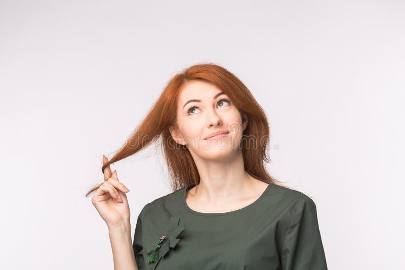Ausdruck- und Leutekonzept - Porträt einer schönen jungen Frau mit dem roten Haar denkend über weißem Hintergrund stockbild