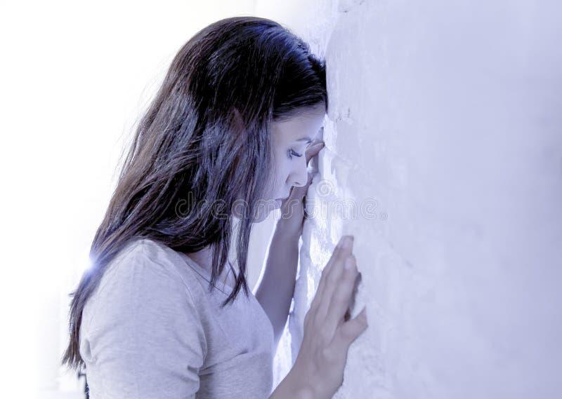 Ausdrucksvolles Porträt der jungen traurigen und deprimierten hispanischen Frau mit Kopf gegen die Wand, die hoffnungslos und in  stockfotografie