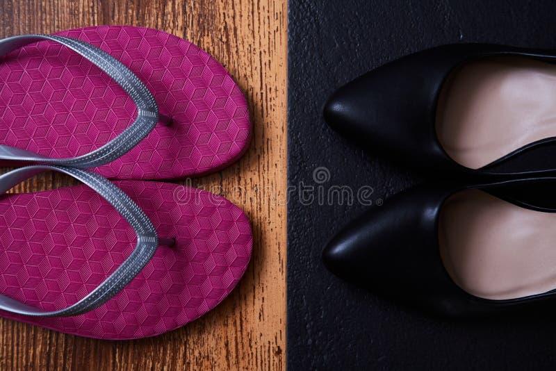 Auserlesenes Konzept der Arbeitsleben-Balance: farbige Sandalen oder Flipflops und strenge schwarze Büroschuhe lizenzfreies stockbild