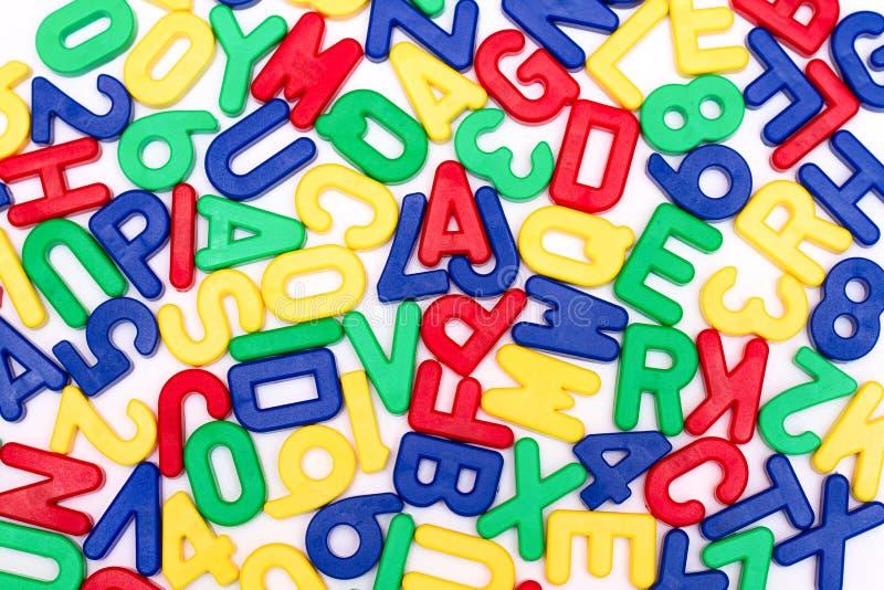 Ausführliche Plastikbuchstaben auf einem Reinweißhintergrund stockbilder