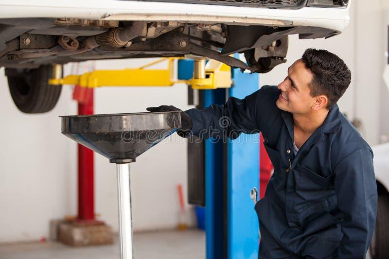 Ausführung eines Ölwechsels auf einem Auto stockfoto