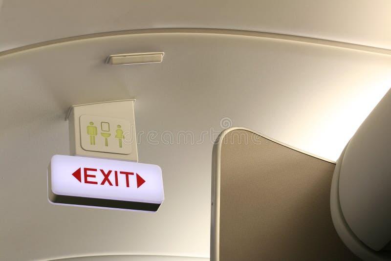 Ausgangs- und Toilettenzeichen an Bord des Flugzeuges lizenzfreie stockfotos