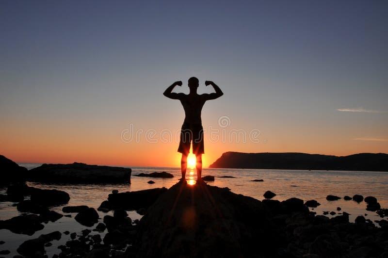 Ausgebildetes Schattenbild des männlichen Körpers auf dem Strand bei Sonnenuntergang lizenzfreie stockbilder