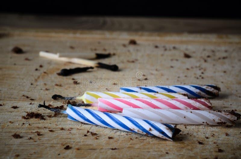Ausgebrannte Geburtstags-Kerzen und Match mit Schokoladen-Kuchen Crum stockfotografie