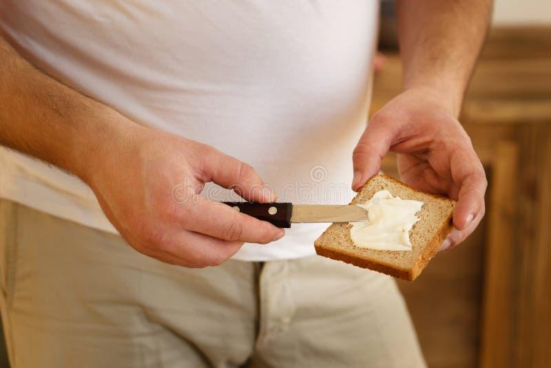 Ausgebreitete Mayonnaise des überladenen Mannes auf Brot lizenzfreie stockbilder