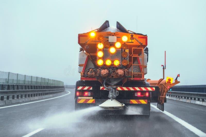 Ausgebreitetes Enteisungssalz des orange Landstraßenwartung Gritter-LKWs auf Straße im Winter lizenzfreies stockbild
