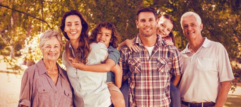 Ausgedehnte glückliche Familie, die zusammen im Park steht stockbild