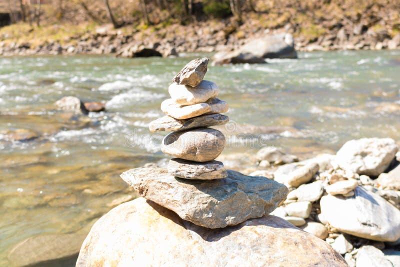 Ausgeglichene Steinpyramide auf r blauem Wasser von Gebirgsfluss chi lizenzfreies stockbild