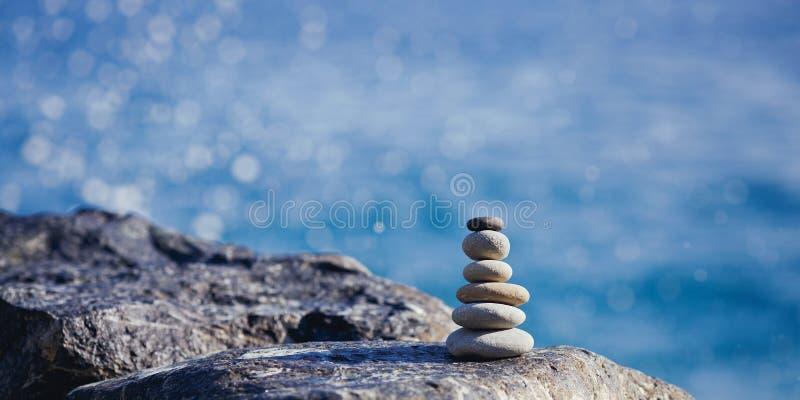 Ausgeglichene Steinpyramide auf Ufer des blauen Wassers Badekurort entsteint Behandlungsszene, Zen wie Konzepte Kieselturm auf de lizenzfreies stockfoto