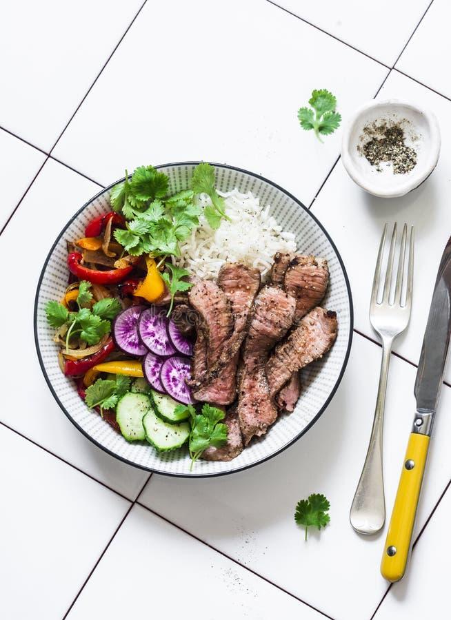 Ausgeglichenes Mittagessen - gegrilltes Rindfleischsteak, Gemüse und Reis auf einem hellen Hintergrund, Draufsicht lizenzfreies stockfoto