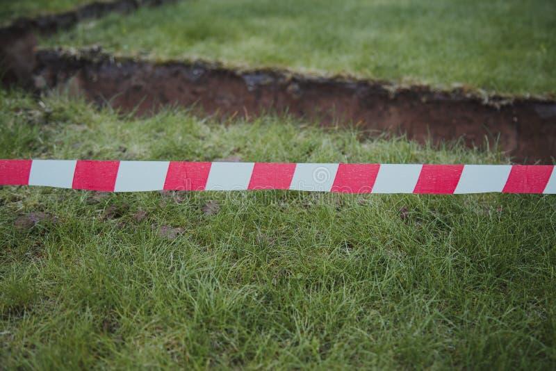 Ausgegrabener Boden unter der Grundlage des Hauses, eingezäunt mit einem roten warnenden Band stockfotografie