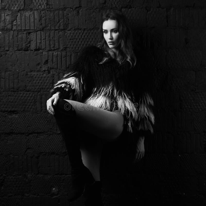 Ausgezeichnete Brunettefrau, die im Fauxpelzmantel am Studio aufwirft stockfotos