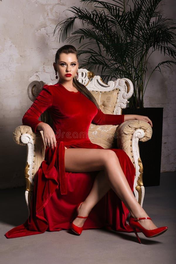 Ausgezeichnete junge Frau im luxuriösen roten Kleid und im kostbaren Schmuck sitzt in einem Stuhl in einer Luxuswohnung Klassisch stockfotos