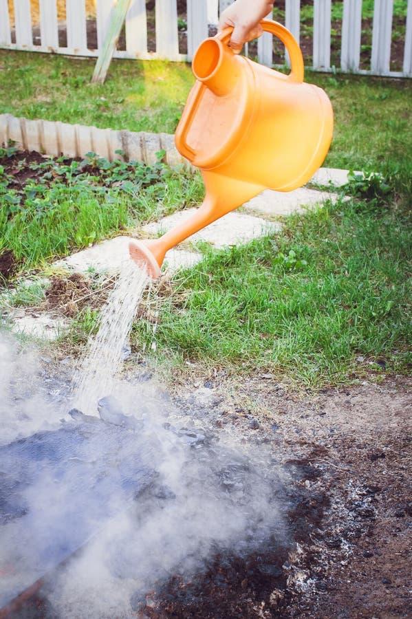 Auslöschung des Feuers mit Wasser von einer Gießkanne an der Datscha stockfotografie