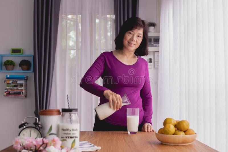 Auslaufende Milch der asiatischen älteren Frau auf Küchentisch Helles Aquarellstillleben lizenzfreies stockbild