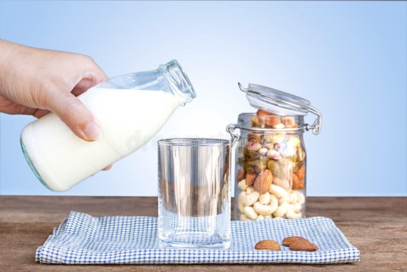 Auslaufende Milch der Frau in ein Glas und in eine Flasche Trockenfrüchte, var lizenzfreie stockbilder