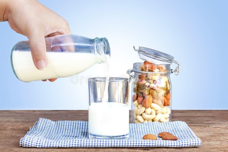 Auslaufende Milch der Frau in ein Glas und in eine Flasche Trockenfrüchte, var stockbilder